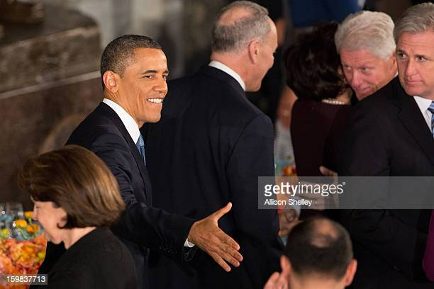S President Barack Obama shakes hands as he and first lady Michelle Obama arrive at the Inaugural Luncheon in Statuary Hall on Inauguration day at...