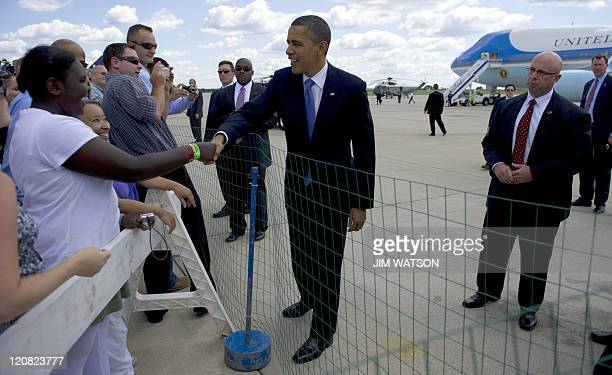 US President Barack Obama shakes hands as he arrives at Gerald Ford International Airport in Grand Rapids Michigan August 11 2011 Obama takes his...