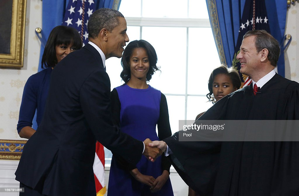 President Barack Obama (2nd L) shakes hands U.S. Supreme Court Chief Justice John Roberts (R) after the oath of office as first lady Michelle Obama (L), daughter Malia (C) and Sasha (2nd R) looks on in the Blue Room of the White House January 20, 2013 in Washington, DC. Obama and U.S. Vice President Joe Biden were officially sworn in a day before the ceremonial inaugural swearing-in.