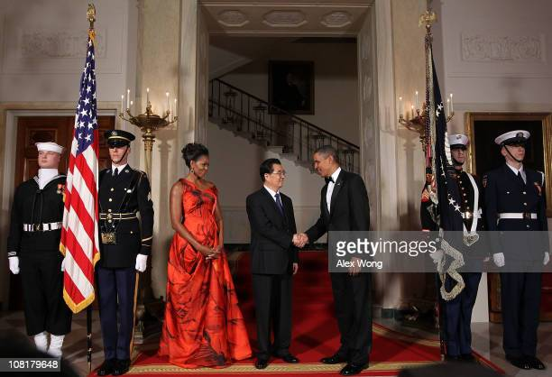 President Barack Obama shakes hands with Chinese President Hu Jintao as first lady Michelle Obama looks on as they pose for the official photo at the...