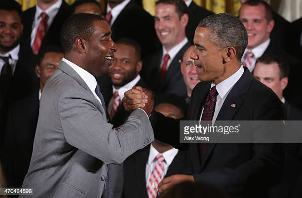 S President Barack Obama shakes hands with former team player Cris Carter as he hosts the Ohio State University Buckyes football team during an East...