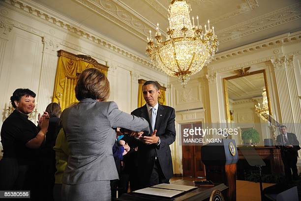 US President Barack Obama shakes hands with House Speaker Nancy Pelosi before signing an executive order to create the White House Council on Women...