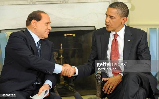 US President Barack Obama shakes hands with Italian Prime Minister Silvio Berlusconi during a meeting in the Oval office at the White House in...