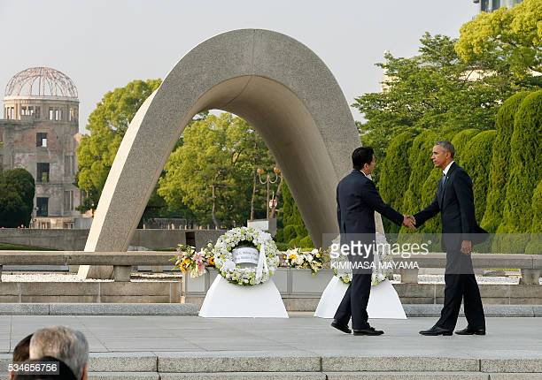 US President Barack Obama shakes hands with Japanese Prime Minister Shinzo Abe after laying a wreath in front of the cenotaph to offer a prayer for...