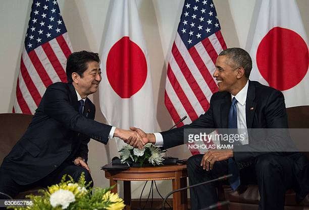 US President Barack Obama shakes hands with Japanese Prime Minister Shinzo Abe December 27 2016 during a meeting in Honolulu Hawaii prior to visiting...