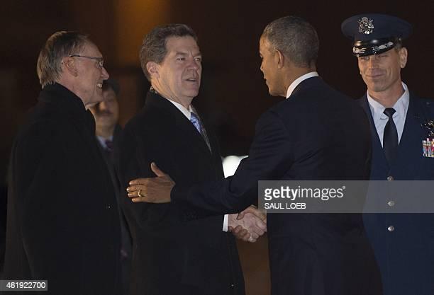 US President Barack Obama shakes hands with Kansas Governor Sam Brownback alongside Topeka Mayor Larry Wolgast upon arrival on Air Force One at...