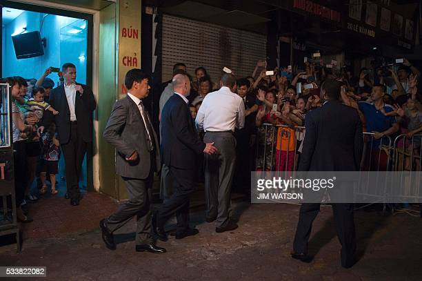 US President Barack Obama shakes hands with locals after eating dinner at Bun cha Huong Lien with CNN's Anthony Bourdain in Hanoi late on May 23 2016...