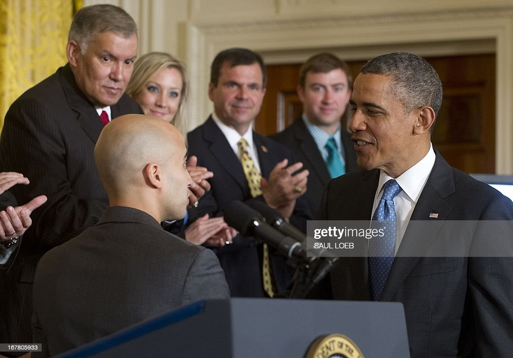 US President Barack Obama shakes hands with military veteran David Padilla during an event highlighting Joining Forces hiring initiative for military veterans and spouses in civilian jobs in the East Room of the White House in Washington, DC, on April 30, 2013. Since President Obama challenged American businesses to hire US military veterans and spouses in August 2011, they have hired or trained 290,000 military veterans and spouses and now pledge to hire or train an additional 435,000 veterans and military spouses by 2018. AFP PHOTO / Saul LOEB
