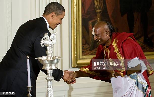 US President Barack Obama shakes hands with Narayanachar Digalakote a Hindu priest after lighting an oil lamp during an event celebrating Diwali in...