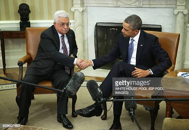 US President Barack Obama shakes hands with Palestinian President Mahmoud Abbas during a meeting in the Oval Office of the White House March 17 2014...