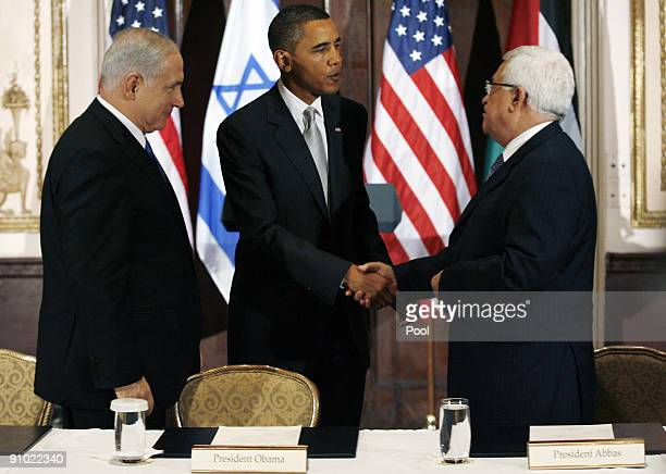 S President Barack Obama shakes hands with Palestinian President Mahmoud Abbas while Israeli Prime Minister Benjamin Netanyahu watches during a...
