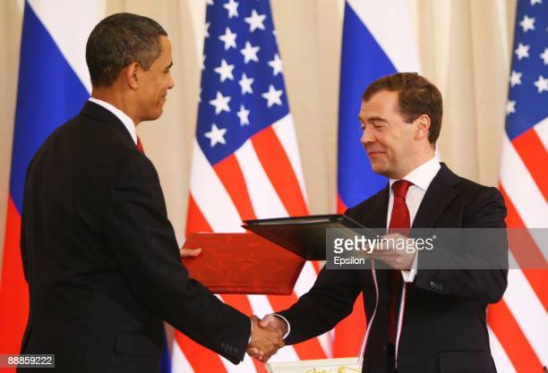 S President Barack Obama shakes hands with Russian President Dmitry Medvedev and exchanges documents as they hold their press conference after the...