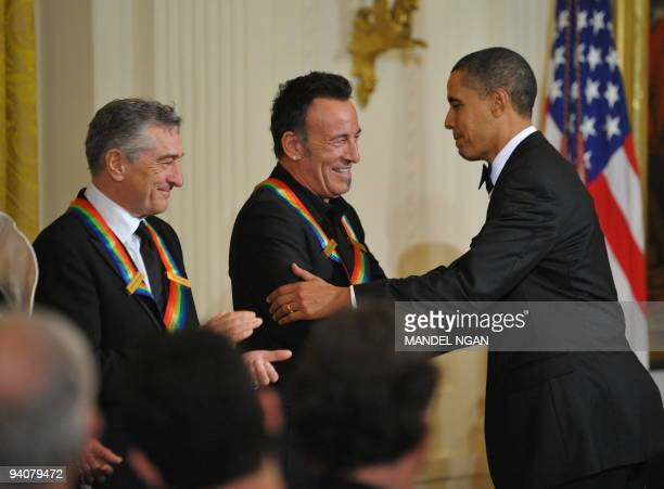 US President Barack Obama shakes hands with singer and songwriter Bruce Springsteen as actor director and producer Robert De Niro looks on during a...