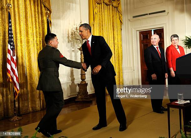 S President Barack Obama shakes hands with USMC Lance Cpl Byron Acevedo as US Citizenship and Immigration Services Director Alejandro Mayorkas and...
