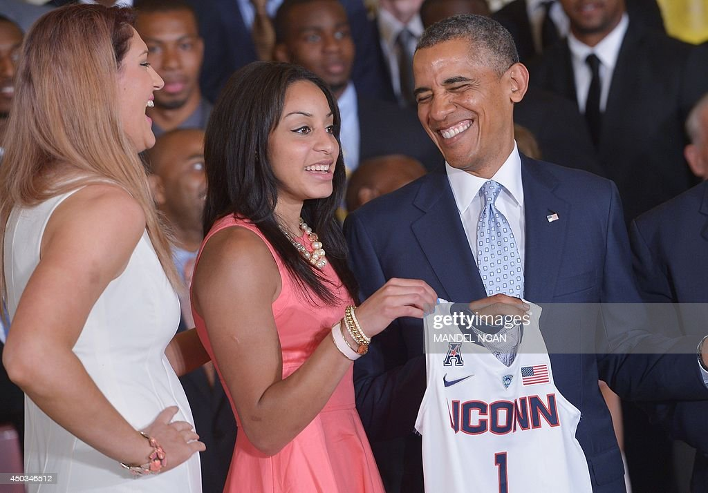 US President Barack Obama (R) shares a laugh with Stefanie Dolson (L) and Bria Hartley while posing with a jersey during an event n honor of the NCAA 2014 Champions, the UConn Huskies Mens and Womens Basketball teams in the East Room of the White House June 9, 2014 in Washington, DC. AFP PHOTO/Mandel NGAN