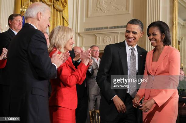 President Barack Obama shares a moment with first lady Michelle Obama as Vice President Joseph Biden and Biden's wife Jill look on during an event to...