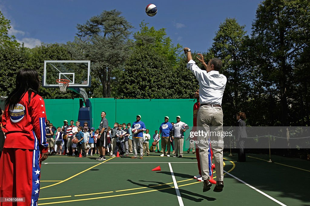 U.S. President Barack Obama (R) shoots a basketball as members of the Harlem Globetrotters look on during the annual Easter Egg Roll on the White House tennis court April 9, 2012 in Washington, DC. Thousands of people are expected to attend the 134-year-old tradition of rolling colored eggs down the White House lawn that was started by President Rutherford B. Hayes in 1878.