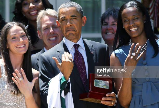 S President Barack Obama shows off a champion ring which he receives as a gift with Seattle Storm's forward guard Sue Bird Coach Brian Agler and Swin...