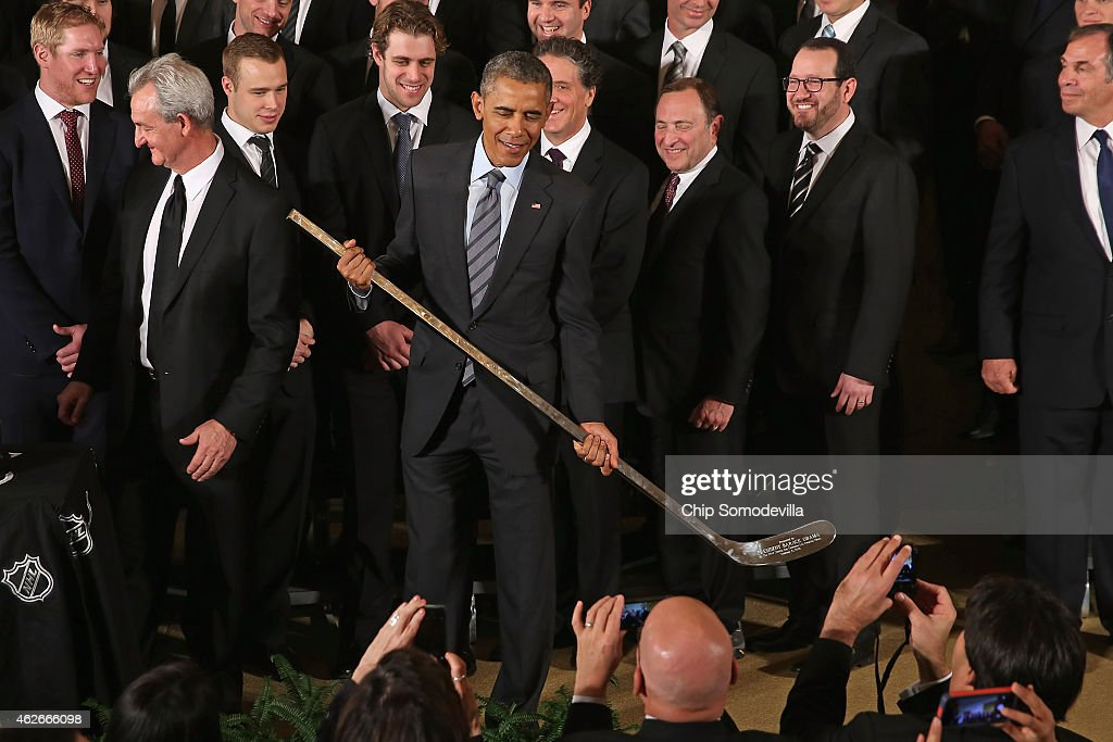 U.S. President Barack Obama shows off the silver hockey stick he was given by Los Angeles Kings Head Coach Darryl Sutter (L) as Obama hosted the National Hockey League champions in the East Room of the White House February 2, 2015 in Washington, DC. Obama simultaneously hosted the Major League Soccer champions Los Angeles Galaxy. Both teams are owned in part by billionaire and The Weekly Standard publisher Philip Anschutz.