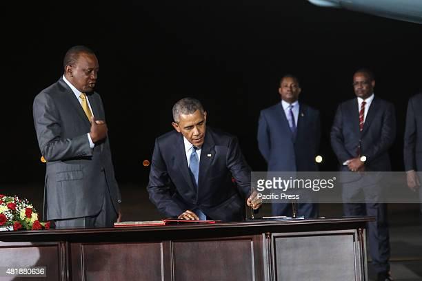 President Barack Obama signs a guest book next to Kenyan President Uhuru Kenyatta at Jomo Kenyatta International Airport in Nairobi Kenyan capital US...