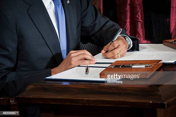 US President Barack Obama signs an Executive Order and a Presidential Memorandum at an event marking Equal Pay Day in the East Room of the White...