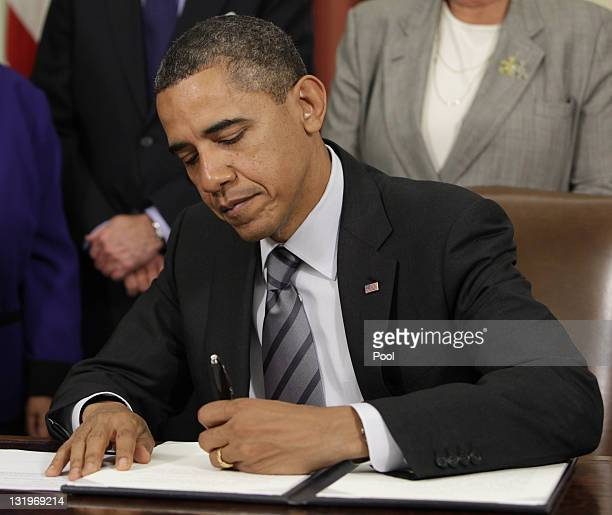 S President Barack Obama signs an Executive Order to cut waste and promote efficient spending across the federal government in the Oval Office at the...