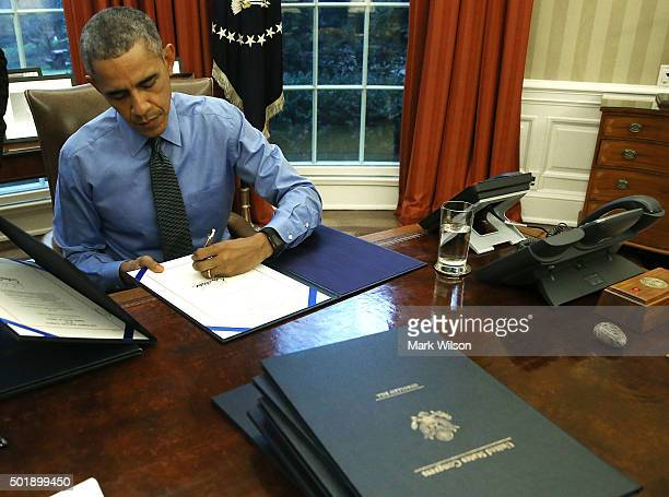 S President Barack Obama signs one of 12 bills at his desk in the Oval Office at the White House December 18 2015 in Washington DC Later today...