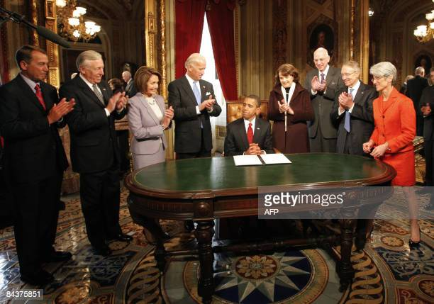 US President Barack Obama signs one of his first acts as President infront of members of the Joint Congressional Committee on Inaugural Ceremonies...