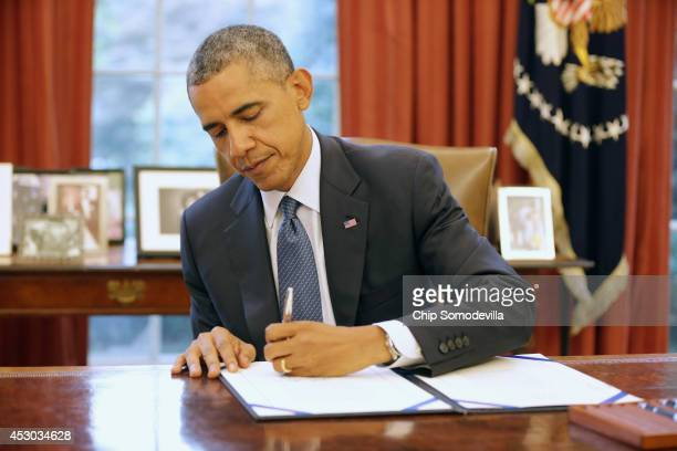 S President Barack Obama signs S 517 Unlocking Consumer Choice and Wireless Competition Act in the Oval Office at the White House August 1 2014 in...