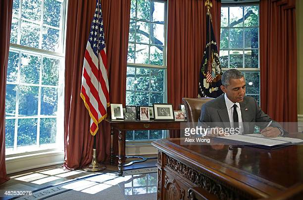 President Barack Obama signs the 3-month extension of the Highway bill in the Oval Office of the White House July 31, 2015 in Washington, DC....