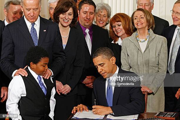 S President Barack Obama signs the Affordable Health Care for America Act during a ceremony with fellow Democrats including Vice President Joe Biden...