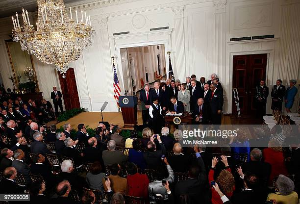 S President Barack Obama signs the Affordable Health Care for America Act during a ceremony with fellow Democrats in the East Room of the White House...