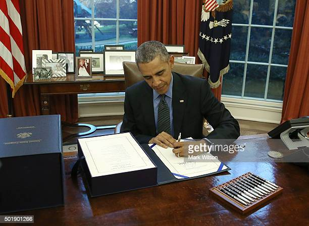 S President Barack Obama signs the budget bill that will fund the government until next September in the Oval Office at the White House December 18...