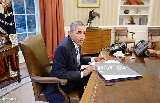 President Barack Obama signs the Department of Homeland Security funding bill in the Oval Office of the White House March 4, 2015 in Washington, DC....
