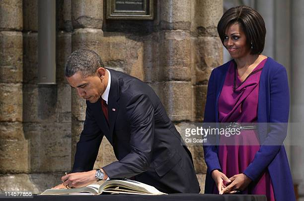 S President Barack Obama signs the Distinguished Visitor's Book in Westminster Abbey next to first lady Michelle Obama on May 24 2011 in London...