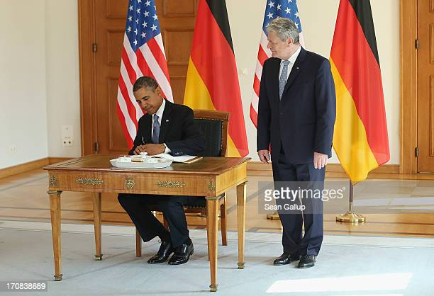 President Barack Obama signs the official guest book as German President Joachim Gauck looks on at Bellevue Palace on June 19, 2013 in Berlin,...