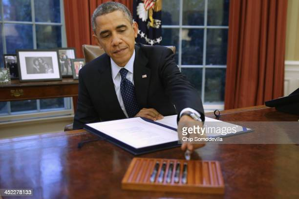 S President Barack Obama signs three bills into law on the Resolute Desk inside the Oval Office at the White House November 27 2013 in Washington DC...