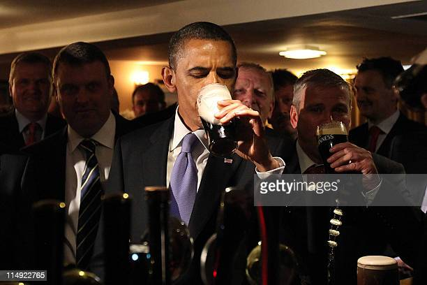 US President Barack Obama sips a Guinness at a pub as he visits Moneygall village in rural County Offaly Ireland where his greatgreatgreat...