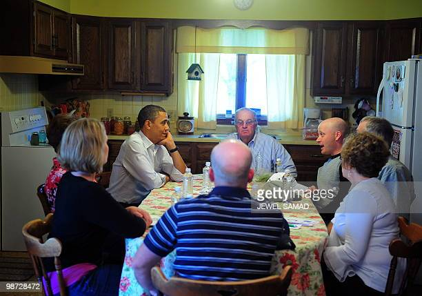 President Barack Obama sits at a kitchen table discussion with the Lowell-Schachtsiek family after visiting Schachtsiek farm in Palmyra, Missouri, on...