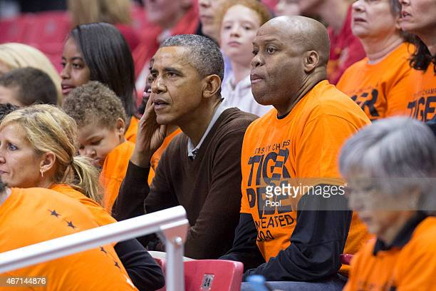 US President Barack Obama sits beside his brotherinlaw Craig Robinson while attending the Green Bay versus Princeton women's college basketball game...