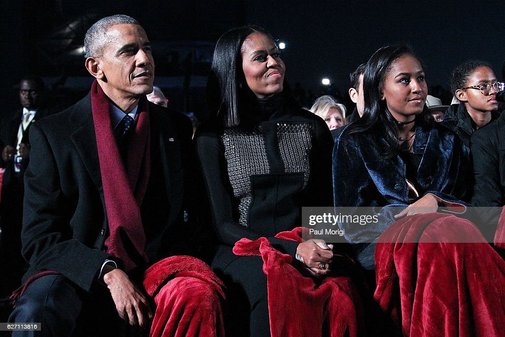 President Barack Obama sits with first lady Michelle Obama (C) and their daughter Sasha (R) to watch musical perfomances during the 94th Annual National Christmas Tree Lighting Ceremony on the Ellipse in PresidentÕs Park on December 1, 2016 in Washington, DC.