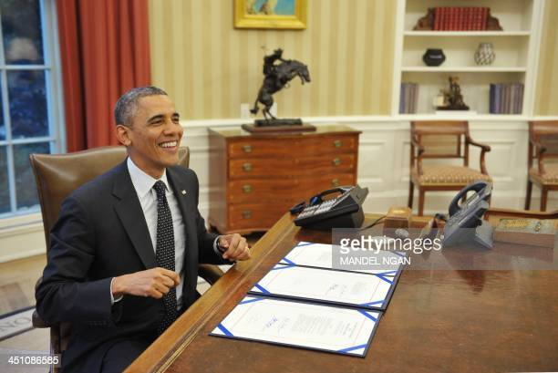 President Barack Obama smiles after signing H.R. 2747: Streamlining Claims Processing for Federal Contractor Employees Act, and S. 893: Veterans...