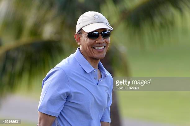 President Barack Obama smiles as he plays golf at Mid-Pacific Country Club in Kailua, Hawaii 2013. The first family is in Hawaii for their annual...