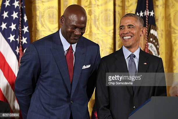 S President Barack Obama smiles up at National Basketball Association Hall of Fame member and legendary athlete Michael Jordan before awarding him...