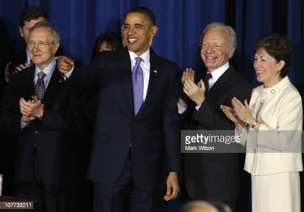 S President Barack Obama smiles while flanked by Senate Majority Leader Harry Reid Sen Joe Lieberman and Sen Susan Collins during a bill signing...