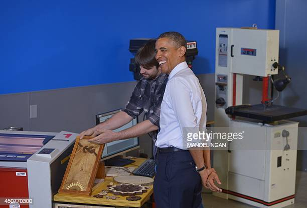 US President Barack Obama smiles while looking at a laser engraving machine during a tour of TechShop Pittsburgh on June 17 2014 in Pittsburgh...