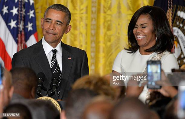 President Barack Obama speaks as First Lady Michelle Obama listens at a reception for Black History Month in the East Room of the White House...