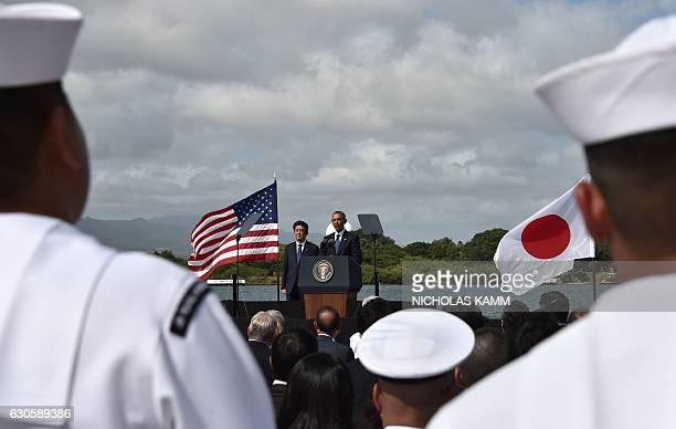 US President Barack Obama speaks as Japanese Prime Minister Shinzo Abe listens at Kilo Pier overlooking the USS Arizona Memorial on December 27 2016...