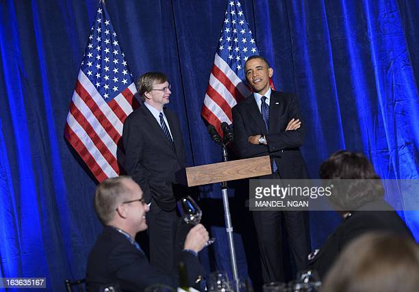 US President Barack Obama speaks as Organizing for Action head Jim Messina looks on during an Organizing for Action dinner on March 13 2013 at the St...