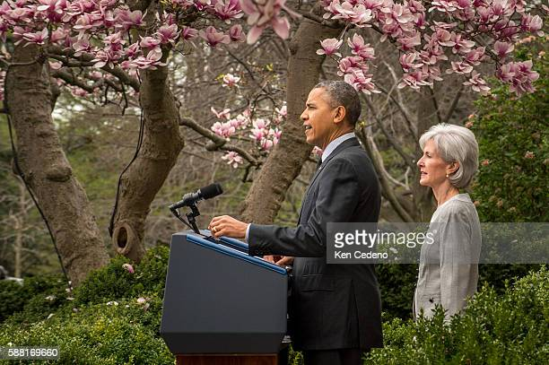 US President Barack Obama speaks as Outgoing Health and Human Services Secretary Kathleen Sebelius looks on in the Rose Garden of the White House...